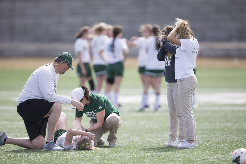 Noelle Vigneri gets treatment from trainer Chelsie Johnson after breaking her leg in a game against Buffalo.